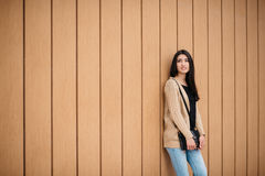 Stylish beautiful woman smiling stands near a wooden wall. Royalty Free Stock Image