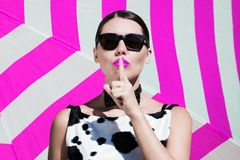 Stylish beautiful woman with sunglasses and  bright painted lips. Showing secret gesture next to a striped background Stock Photography