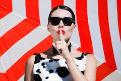 Stylish beautiful woman with sunglasses and  bright painted lips. Showing secret gesture next to a striped background Royalty Free Stock Photo