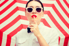 Stylish beautiful woman wearing white chemise and sunglasses. With bright painted lips showing secret gesture next to a striped background Stock Images