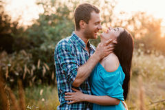 Stylish beautiful young couple standing outdoors at sunset light Stock Photography