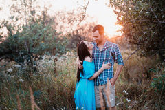 Stylish beautiful young couple standing outdoors at sunset light Stock Photos