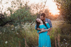 Stylish beautiful young couple standing outdoors at sunset light Royalty Free Stock Images