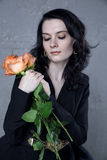 Stylish beautiful young woman with orange roses. In hands Royalty Free Stock Photo