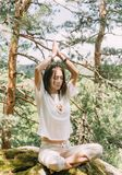 Woman practicing yoga in summer forest. Stylish beautiful young woman practicing yoga on cliff in summer forest outdoor stock photography