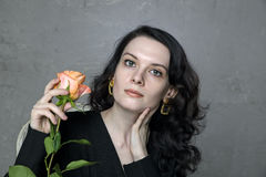Stylish beautiful young woman with rose. Stylish beautiful young woman with orange rose Stock Photography
