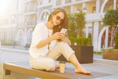 Stylish woman sitting on bench with smartphone. royalty free stock images