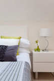 Stylish bedroom detail. With intricate fabrics, cushions, pillows, duvet and side table including lamp Royalty Free Stock Photos