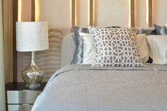 Stylish bedroom interior design with brown pillows on bed and decorative table lamp Royalty Free Stock Photo