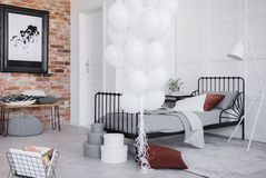 Bedroom interior with grey bedding, bunch of white balloons and black frame on the brick wall, real photo. Stylish bedroom interior with grey bedding, bunch of stock image