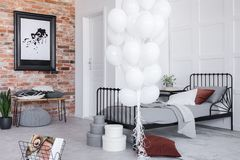 Stylish bedroom interior with grey bedding and white balloons, real photo. Stylish bedroom interior with grey bedding and bunch of white balloons, real photo stock photo