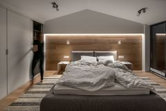 Stylish bedroom in modern style with light walls and luminous lamps. Illuminated modern bedroom with white and wooden walls, parquet with a carpet. There is a stock image