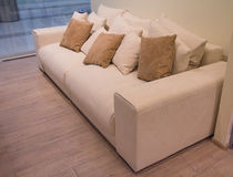 Stylish beige sofa with lots of pillows Royalty Free Stock Photos