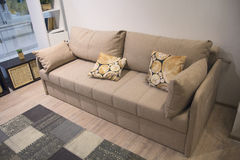 Stylish beige sofa with lots of pillows Stock Image