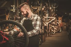 Stylish bicycle mechanic doing his professional work in  workshop. Royalty Free Stock Photography