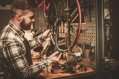 Stylish bicycle mechanic doing his professional work in  workshop. Royalty Free Stock Photo