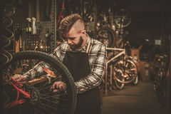 Stylish bicycle mechanic doing his professional work in  workshop Stock Photography