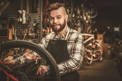 Stylish bicycle mechanic doing his professional work in  workshop. Stock Image