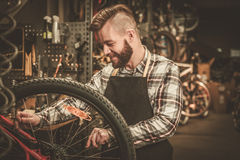 Stylish bicycle mechanic doing his professional work in  workshop Royalty Free Stock Photos