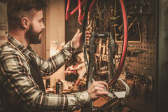 Stylish bicycle mechanic doing his professional work in  workshop Stock Photos