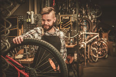 Stylish bicycle mechanic doing his professional work in  workshop Royalty Free Stock Photo