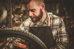 Stylish bicycle mechanic doing his professional work in  workshop Royalty Free Stock Photography