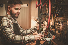 Stylish bicycle mechanic doing his professional work in  workshop Royalty Free Stock Image