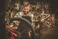 Stylish bicycle mechanic doing his professional work in workshop.  royalty free stock photos