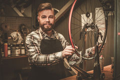 Stylish bicycle mechanic doing his professional work in  workshop Stock Image