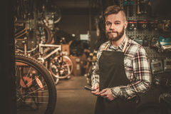 Stylish bicycle mechanic doing his professional work in  workshop Royalty Free Stock Images