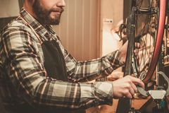 Stylish bicycle mechanic doing  his professional work in workshop. Royalty Free Stock Image
