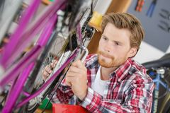 Stylish bicycle mechanic doing professional work in workshop royalty free stock photos