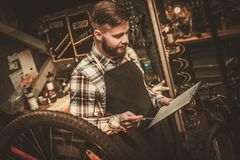 Stylish bicycle mechanic making notes in clipboard in his  workshop. Stock Images