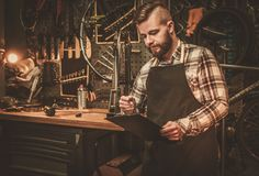 Stylish bicycle mechanic making notes in clipboard in his  workshop. Stock Photos