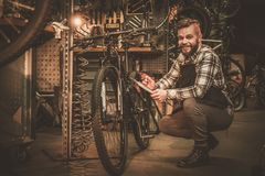 Stylish bicycle mechanic making notes in clipboard in his  workshop. Royalty Free Stock Photography
