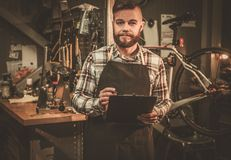 Stylish bicycle mechanic making notes in clipboard in his  workshop. Royalty Free Stock Image