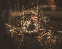 Stylish bicycle mechanic making notes in clipboard in his  workshop. Stock Image