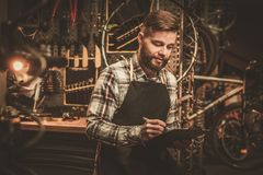 Stylish bicycle mechanic making notes in clipboard in his  workshop. Stock Photo