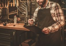 Stylish bicycle mechanic making notes in  clipboard in his workshop. Stock Photography