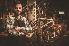 Stylish bicycle mechanic standing in his  workshop. Stock Photography