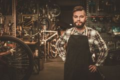 Stylish bicycle mechanic standing in his  workshop. Stock Photo