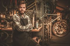 Stylish bicycle mechanic standing in his  workshop. Royalty Free Stock Images
