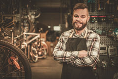 Stylish bicycle mechanic standing in his  workshop. Stock Images