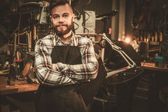 Stylish bicycle mechanic standing in his  workshop. Stock Photos