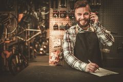 Stylish bicycle mechanic takes order by phone in his  workshop. Stock Image