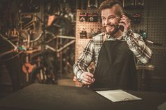 Stylish bicycle mechanic takes order by phone in his  workshop. Royalty Free Stock Image