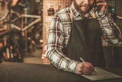 Stylish bicycle mechanic takes order  by phone in his workshop. Stock Photo