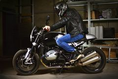 Stylish biker sits on his motorcycle in garage. A Stylish biker sits on his motorcycle in garage royalty free stock photo