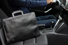 Stylish black business man`s leather bag on the passanger seat near driver in the car with modern interior royalty free stock photography