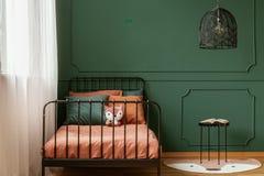 Stylish black chandelier above industrial black metal table with book in dark green teenager bedroom stock photo